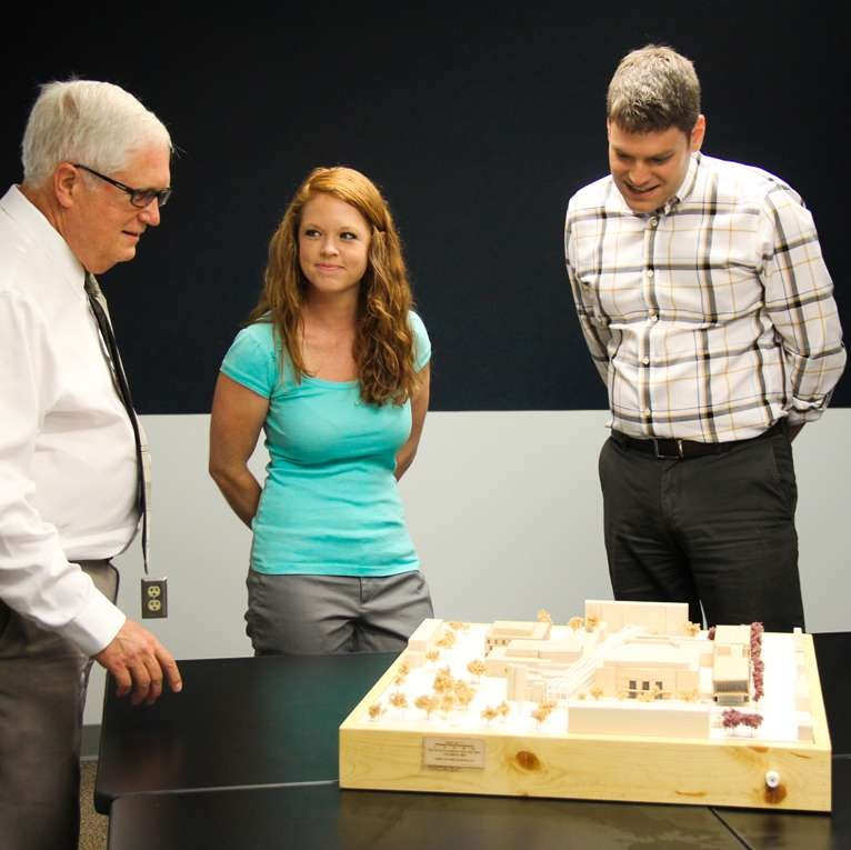 three staff looking at a model of a building with its surrounding landscaping