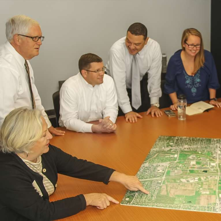 colleagues gathered around a table, looking at and discussing a site plan of the university