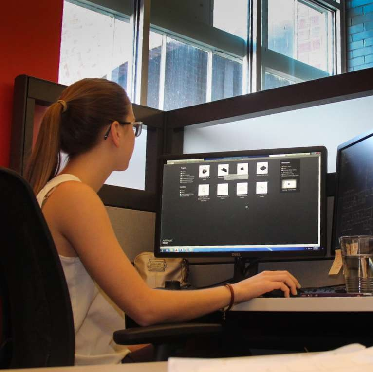 female student sitting at a computer screen, operating the mouse