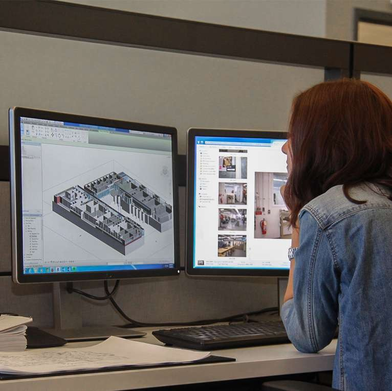 female student sitting at a computer screen, looking at a 3D image of a building